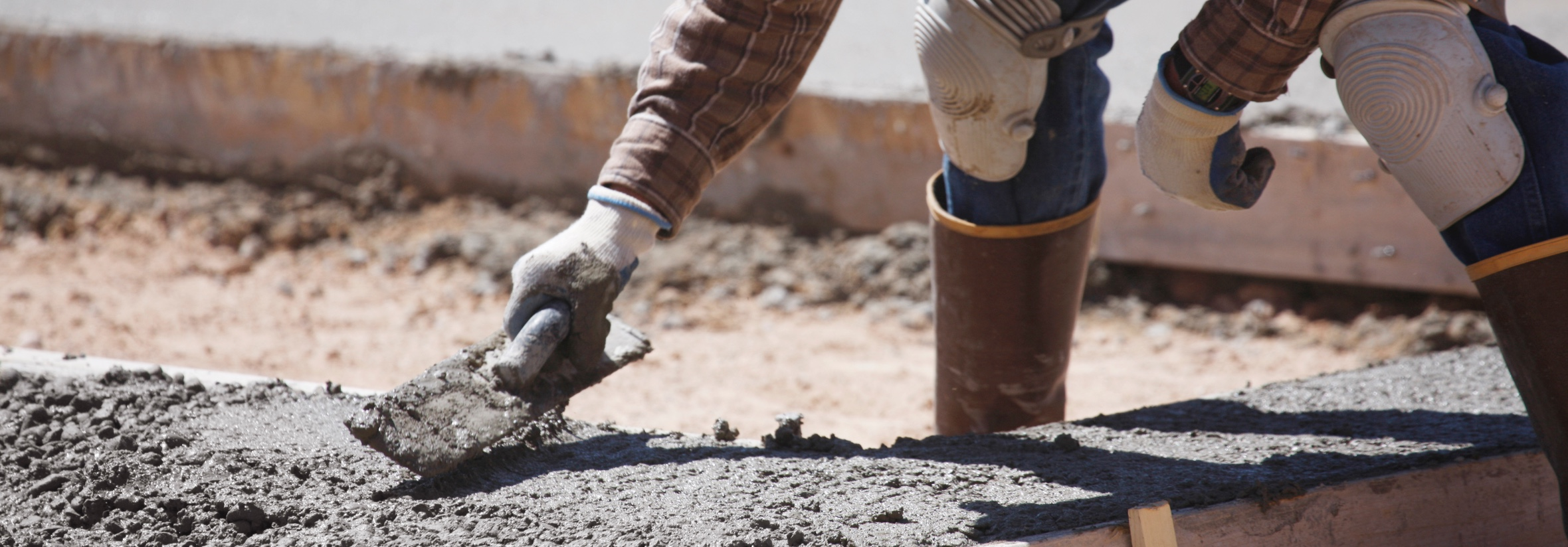 worker in rubber boots applies concrete with trowel